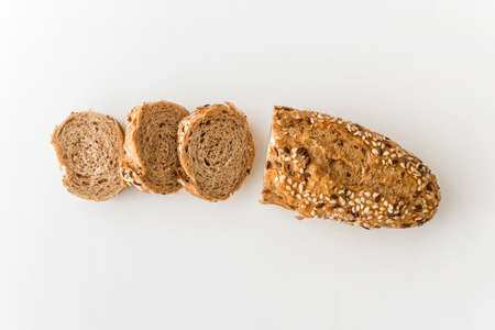 Wholegrain sliced freshly baked bread with flax and sesame seeds on white background. Top view.