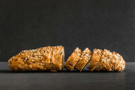 Wholegrain sliced freshly baked bread with flax and sesame seeds on black background. Side view.