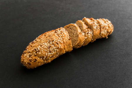Wholegrain sliced freshly baked bread with flax and sesame seeds on black background. Top view