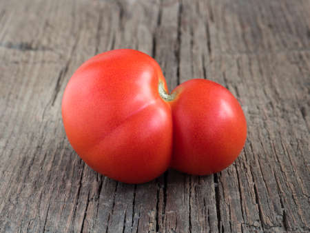 Fresh ugly red farm tomato on wooden background. Trendy vegetarian vegetables. Healthy food 写真素材