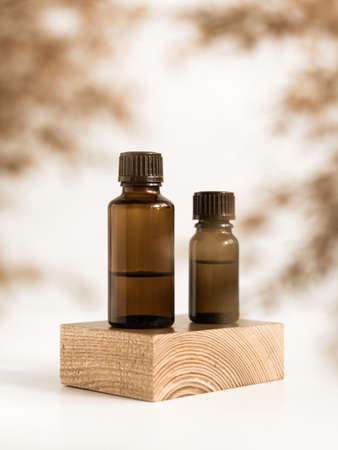 Bottles essential oils on wooden stand on white background. Hemp oil. CBD cannabis products. Minimalistic fragrant concept. Natural medicine