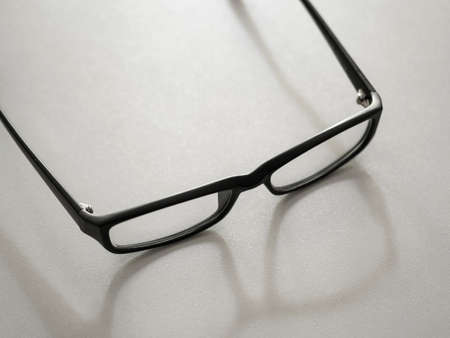 Black glasses and their shadow on gray background.