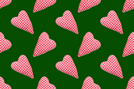 Christmas seamless pattern. Top view soft red heart pads on green background. Love concept flat lay
