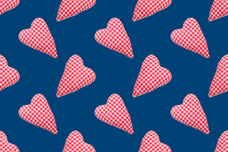Christmas seamless pattern. Top view soft red heart pads on blue background. Love concept flat lay Фото со стока