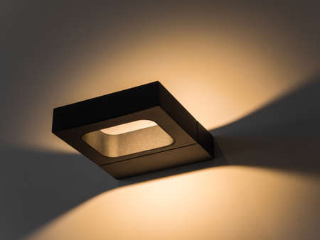 Sconce. Modern minimalist black square wall lamp shines with yellow light. Internal lighting. Close-up. Beautiful geometric shadows