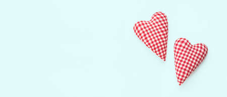 Valentines day banner. Two soft red hearts on pastel blue background. Flat lay composition. Top view, copy space