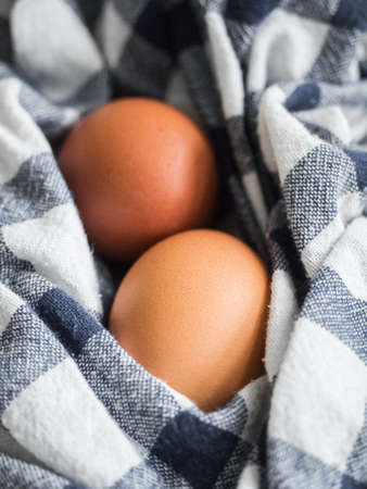 Two beige chicken eggs lie on a checkered mat. Healthy food vertical background. Easter concept. Close-up