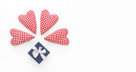 Valentines day composition. Soft red hearts and gift box on white background. Flat lay, top view, copy space Фото со стока