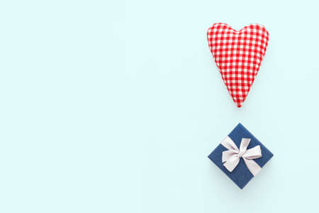 Valentines day composition. Two soft red hearts and gift box on pastel blue background. Flat lay, top view, copy space