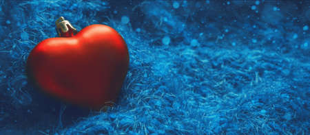 Festive winter concept banner. Red heart-shaped christmas tree toy on fabulous blue background with bokeh. New Year, Christmas or Valentines day background. Copy space