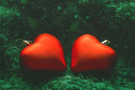 Festive winter concept banner. Two red heart-shaped christmas tree toys on fabulous green background with bokeh. New Year, Christmas or Valentines day background. Copy space Фото со стока