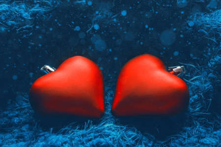 Festive winter concept banner. Two red heart-shaped christmas tree toys on fabulous blue background with bokeh. New Year, Christmas or Valentines day background. Copy space Фото со стока