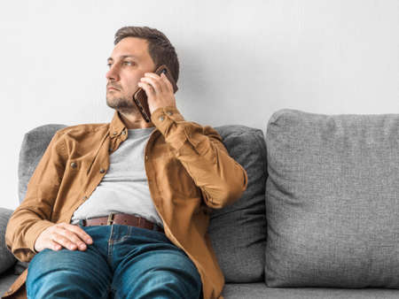 Middle aged man in beige shirt and jeans sits at home on gray sofa and calls on the phone. Smartphone in hand near the ear. Online business or remote work concept