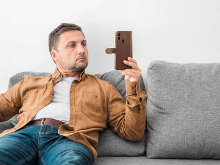 Middle aged man in beige shirt and jeans sits at home on gray sofa and looks intently at the phone. Smartphone in hand. Blogging, online education or remote work concept. Фото со стока