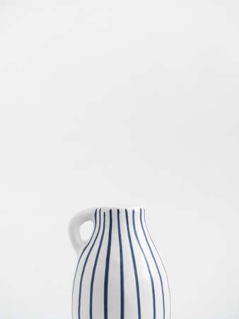 White ceramic jug with blue stripes isolated on white background. Trend minimalistic composition. Boho or Scandinavian style poster in modern home interior. Copy space. Close-up