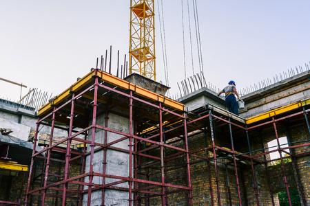 Arbeiten auf der Baustelle. Bau des Gebäudes aus gelbem Backstein. Baulöss und Kran. Mauern bauen