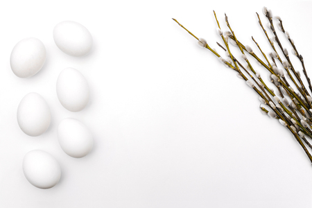 Flowering willow branches. Willow branches and eggs on a white background. Spring card template. Place for text