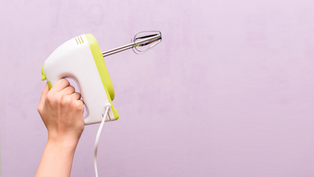 Female hand is holding a mixer. Kitchen electric appliance on a purple background. Woman housewife. Empty space for text