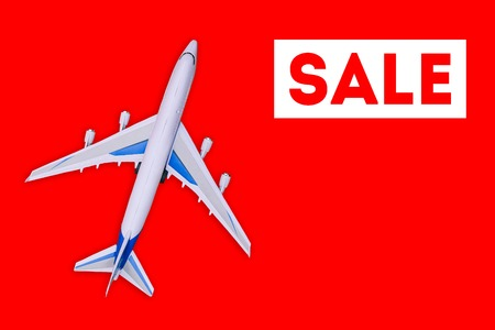 Travel and tourism concept. . Sale of air tickets and travel vouchers. Passenger aircraft on a red background 写真素材
