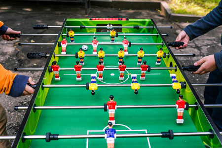 A game of table football. Two people playing table football outside. Entertainment during holidays or free time. Young people on holiday in summer