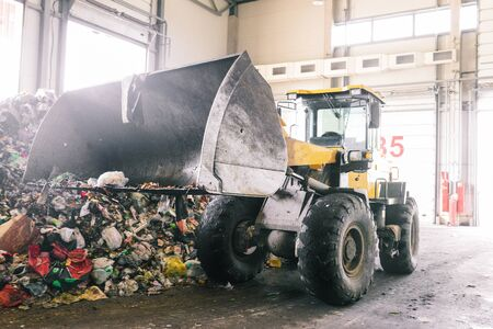 Hangar automated plant for sorting household waste. An excavator with a raised bucket collects and transports trash for recycling. Sorting