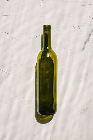 Empty bottle against white background. Hard shadows and reflection from the bottle. Minimal style. Art gallery, art. View from above