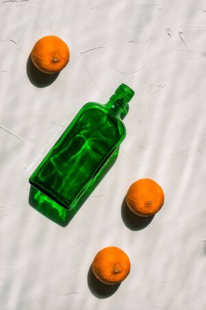Green empty bottle and three mandarins on a white background. Minimal still life. Bright light, hard shadows and a reflection from the bottle. Creative style, art gallery. View from above