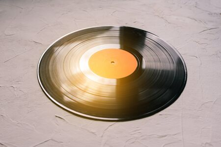 Vinyl record on a white background and sun rays. Analog sound. Music background. The concept of music, parties.