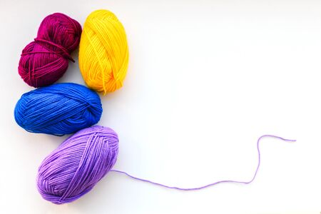 Balls of thread for knitting. Knitting threads on a white background. Materials to do the work at home. Multi-colored balls of thread for needlework. Copy space Stock Photo