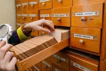 A man is looking for information in a box with paper cards. Search for data and information. Data storage in the library or in the office. Database.