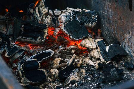 Braises fumantes d'un incendie. Extinction du feu de joie. La texture de la braise agrandi. Saison de barbecue au charbon de bois décrépite. Banque d'images