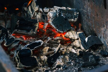 Smoldering embers from a fire. Extinguishing bonfire. The texture of the embers closeup. Decrepit charcoal barbecue season. Banque d'images