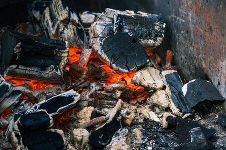 Coal in the fireplace. Extinguishing bonfire after burning wood. Cooking on fire. Smoldering charcoal.