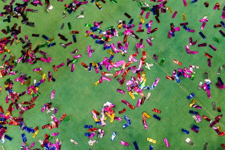 Colorful pieces of confetti are scattered on the green carpet. Celebratory background for a birthday, anniversary, carnival or party.