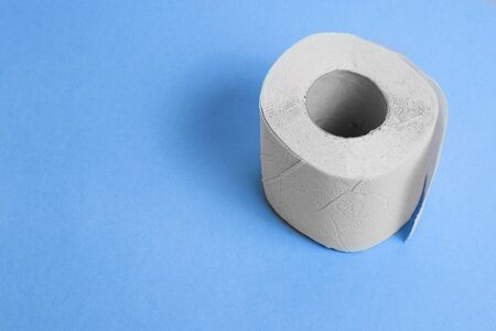 Toilet paper on a blue background. Sanitary and household supplies. Room cleaning. Copy space