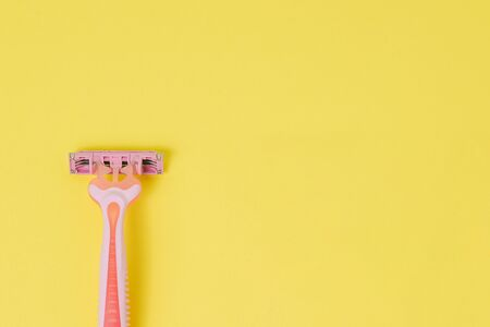 Female razor for depilation on a yellow background. Pink disposable razor. Top view, copy space