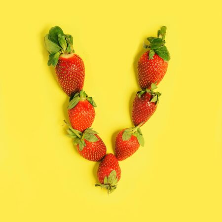 Letter L made from Strawberries on a yellow background. Fruit alphabet