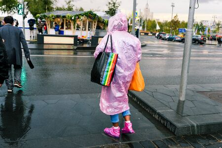 Pedestrian crossing on a busy street in Moscow. Rainy weather. People with umbrellas cross the road to a green traffic light. Man bright raincoat.
