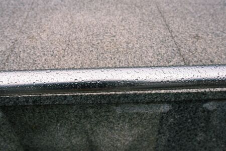Metal railing on the street after the rain. Stainless steel with water drops close-up