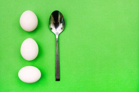 White eggs and spoon on a green background. Breakfast concept, soft-boiled egg. International cuisine, food. Top view, copy space