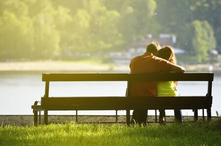 Rear view of a young couple sitting on a park bench. Romantic silhouette of people in love
