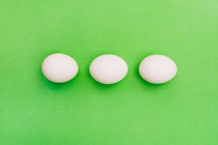 Three white chicken eggs on a green background. Breakfast concept, soft-boiled egg. International cuisine, food. Top view, flat lay.