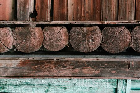 Wall of an old wooden house. Round wood bars and planks. Stock Photo