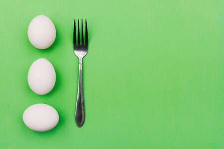 White eggs and fork on a green background. Breakfast concept, soft-boiled egg. International cuisine, food. Top view, copy space