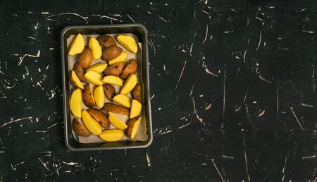 Sliced potatoes in slices lies in a baking dish in the oven. Cooking for lunch, dinner or a festive feast. Flat lay, copy space