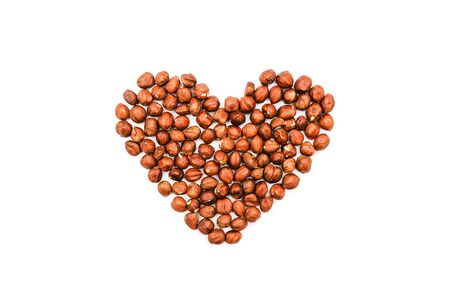 Heart shape made of nuts. Brown hazelnut kernels on a white background.