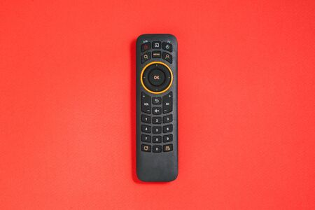 Remote control with buttons on a red background. Smart TV concept. Home entertainment