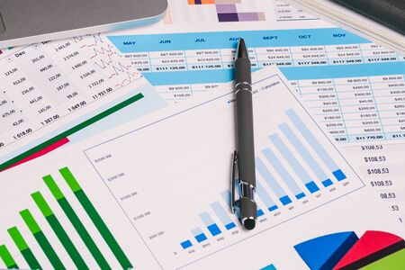 Statistical charts and a pen on the businessmans desktop. Calculation of income and expenses. Accounting indicators, audit and data analysis. Business, Finance and accounting concepts.