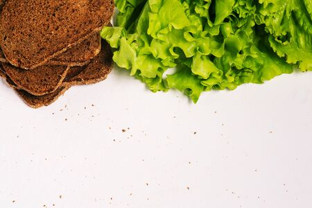 Sliced bread and fresh green leaves on a white background. Healthy food, diet. Top view, copy space
