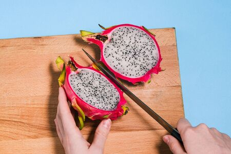 Pitaya cut into two halves. Close-up of female hands cutting summer dragon fruit. Pitaya on a wooden Board with a blue background. Фото со стока